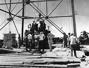 Men stand around a large oil-rig type structure. a large round object is being hoisted up.