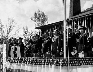 Men in suits and uniforms stand on a dais decorated with bunting and salute.